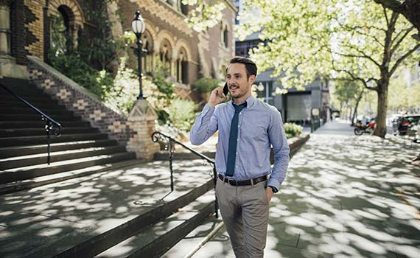 Australasian businesman on commute to work, speaking on mobile phone as he walks