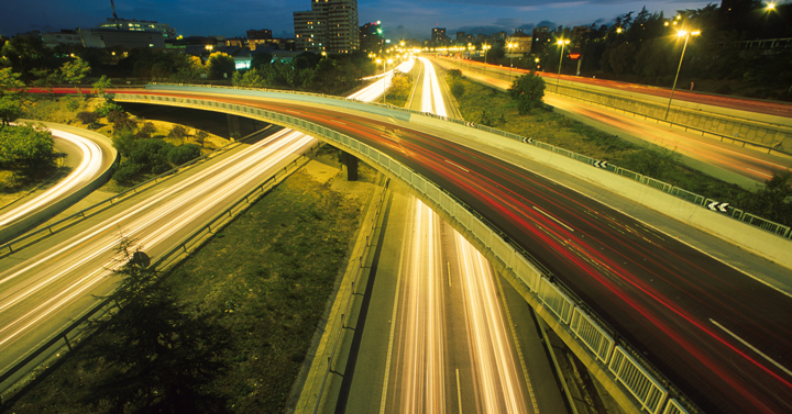 Busy motorway junction at night with blurred headlights streaming light