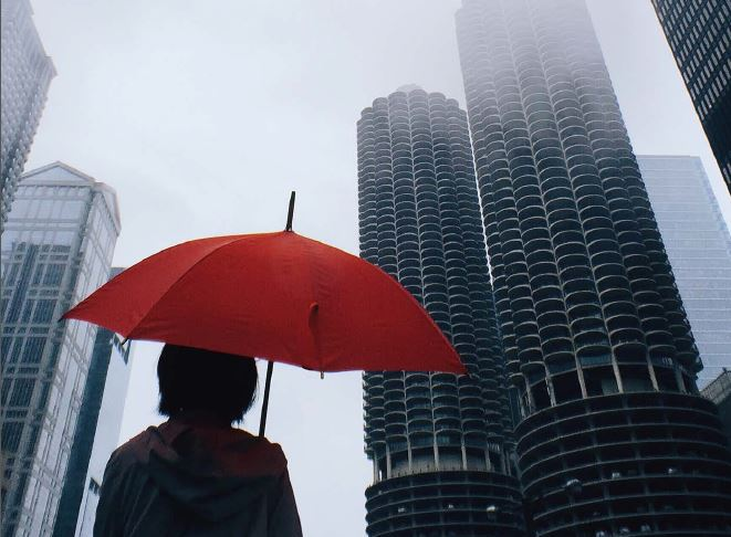 Report cover image of a woman in a city carrying an umbrella