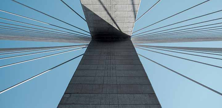 Looking skyward from a modern concrete and steel bridge