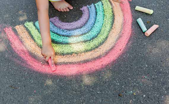 Image of a child drawing a rainbow on a sidewalk that is on the covver of the report.