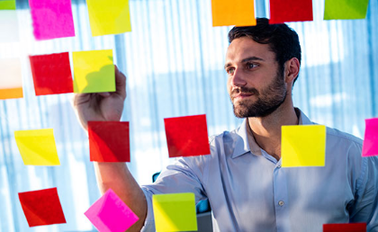 An employee reviewing comments on sticky notes
